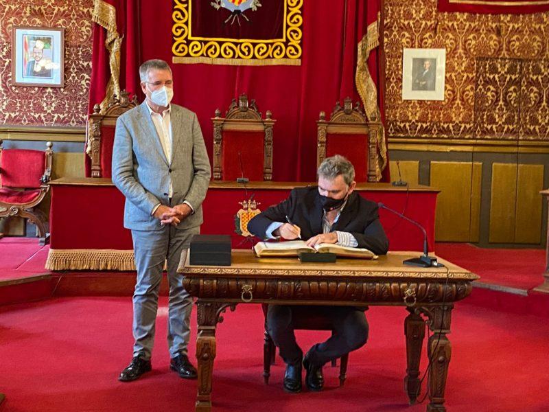 Àngel Òdena signa el llibre d'honor al Saló de Plens de Tarragona, acompanyat de l'alcalde Pau Ricomà.