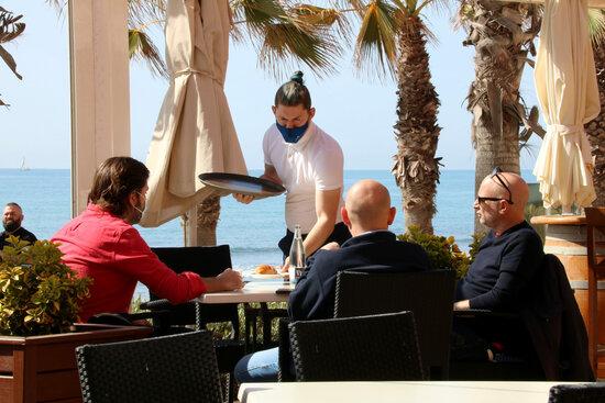 Pla tancat d'un cambrer servint una taula en una terrassa. Foto: ACN.