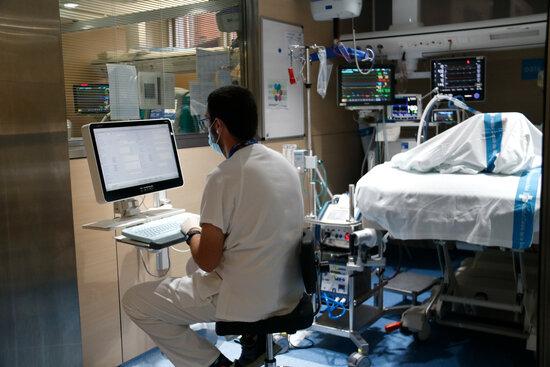 Pla d'un treballador en un box d'UCI covid. Foto: ACN.