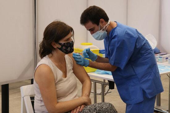 Pla mig d'un infermer administrant una vacuna contra la covid-19 a una dona.