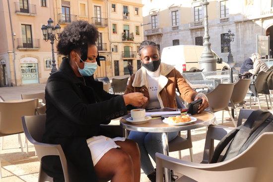 Dues noies fent un cafè en una terrassa de la plaça de la Font. Foto: ACN.